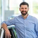 KFZ Händler lehnt an Auto