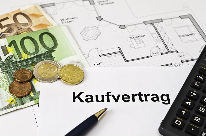 kaufvertrag einer Immobilie und Geld auf dem Tisch