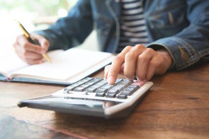 Mann schreibt auf Block & tippt Taschenrechner