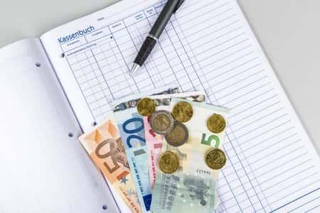 Kassenbuch Gastronomie mit Geld und Stift